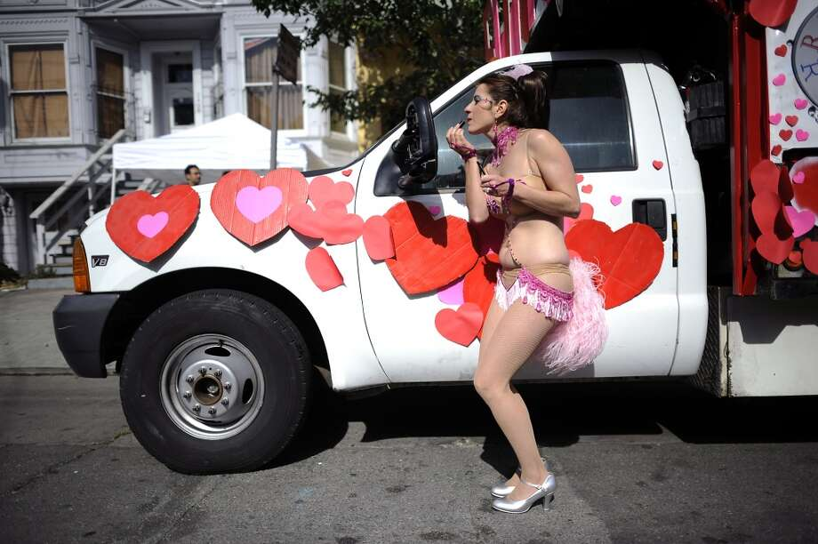 Hot Pink Feathers member Pamela Mendoza uses the side mirror of a truck to apply her lipstick before the start of  the 35th annual Carnaval parade in the Mission District of San Francisco on May 26th, 2013.
