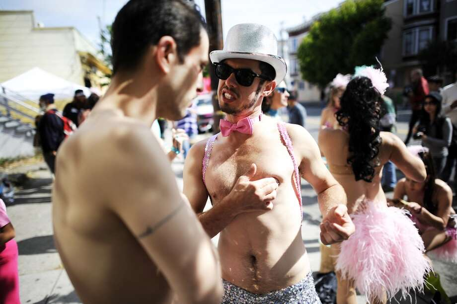 Hot Pink Feathers members Chadd Behavior (right) press on nipple pasties as he and Bobby Barnaby get ready for the 35th annual Carnaval parade in the Mission District of San Francisco on May 26th, 2013.