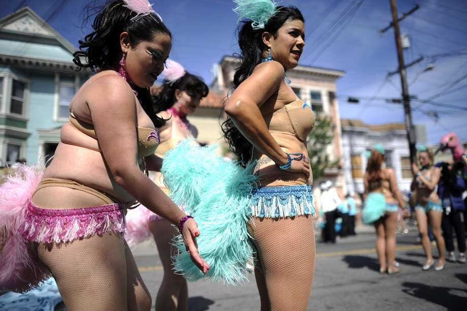 Sarah Benite adjusts the tail feathers of Stephanie Dominguez as their group Hot Pink Feathers gets ready for the start of the 35th annual Carnaval parade in the Mission District  on May 26th, 2013.