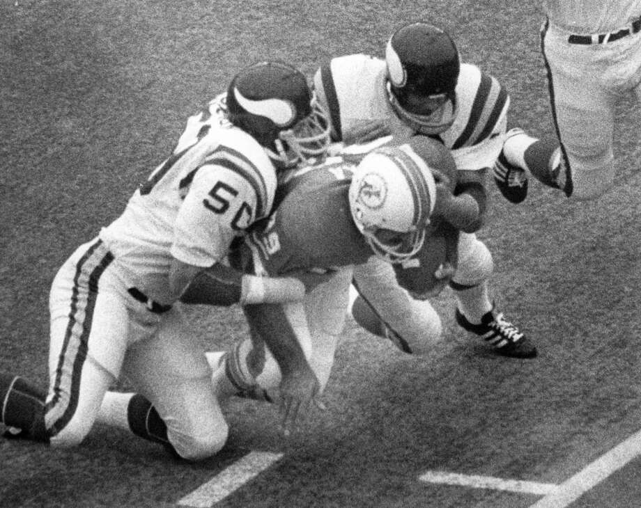 Dolphins running back Larry Csonka goes in for a touchdown while Vikings Jeff Siemon (50) and Paul Krause (22) attempt tackle him.