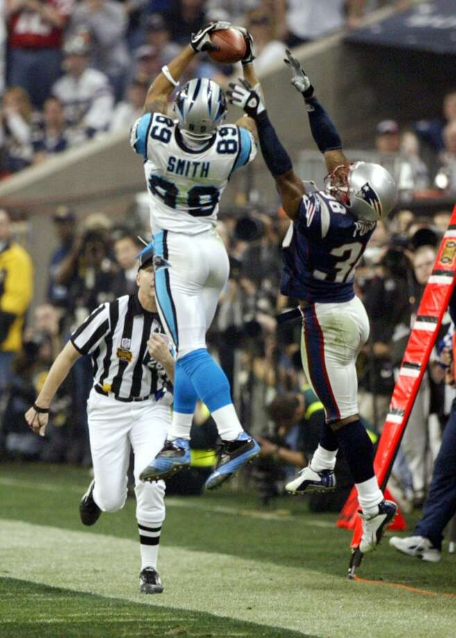 Panthers Steve Smith hauls in a pass against the defense of Patriots cornerback Tyrone Poole during fourth quarter Superbowl XXXVIII.