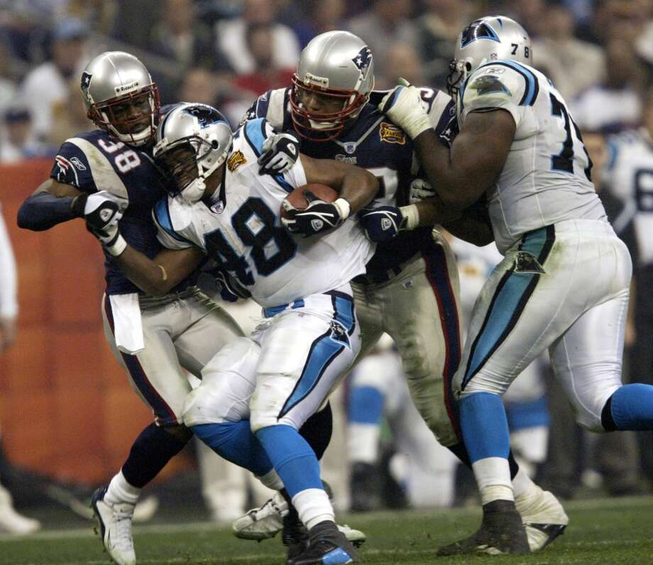 Panthers running back Stephen Davis tries to keep pushing against Patriots defenders Tyrone Poole, left, and Richard Seymour.