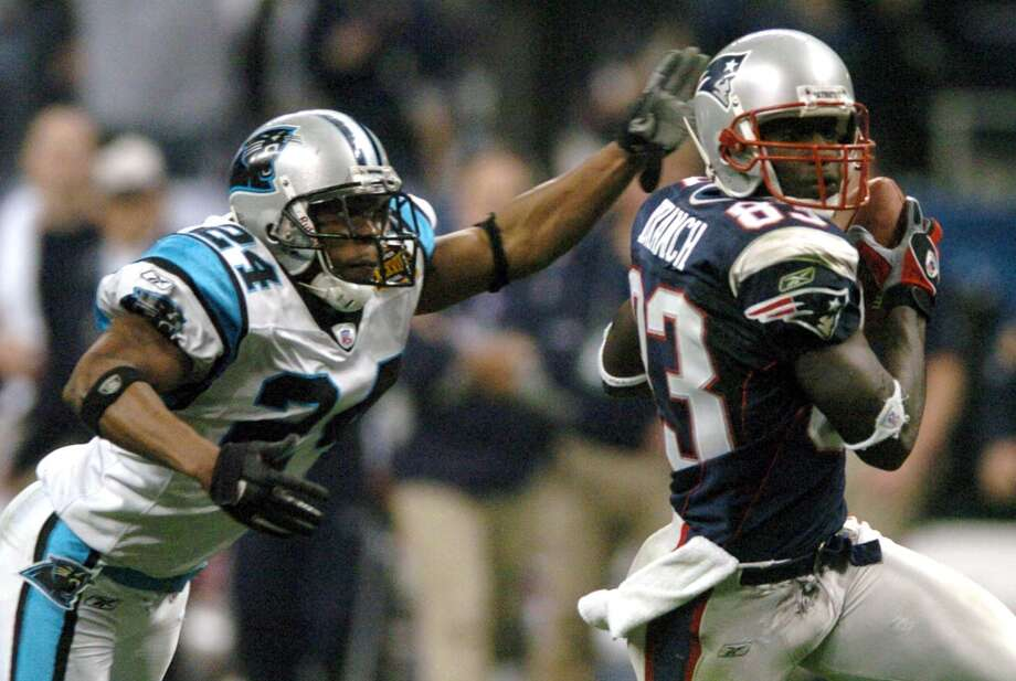 Panthers defensive back Ricky Manning Jr. (24) reaches out to try and tackle Patriots receiver Deion Branch (83) in the second quarter.