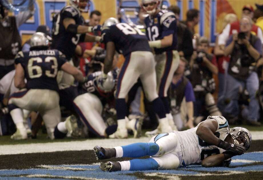 Panthers defensive end Al Wallace lies in the end zone after Patriots linebacker Mike Vrabel (50) scored a touchdown.
