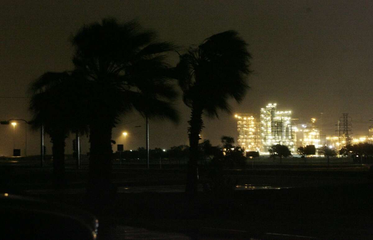 Palm trees along Highway 332 in Lake Jackson sway in the gusty winds from Hurricane Ike as the Dod Chemical Plant is seen hours before landfall on Friday, Sept. 12, 2008, in Surfside Beach. While all of Lake Jackson was in the dark because of power outages, the Dow Chemical Plant remained lit thanks to generators. ( Julio Cortez / Chronicle )