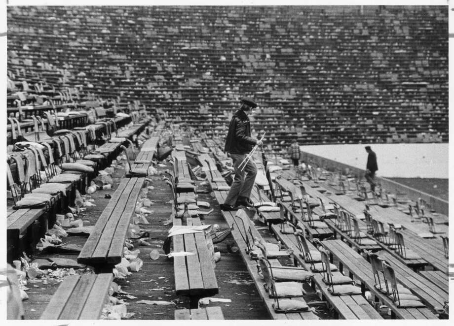 Ushers wade through a sea of trash after Rice Stadium hosted Super Bowl VIII in 1974.  It cost an estimated $25,000 to clean up the stadium and parking lot after the game.