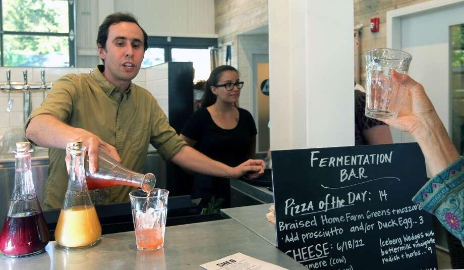 Jordan Lancer, the fermentation bartender, pours a shrub-vinegar drink made with a strawberry, opal basil rose vinegar.