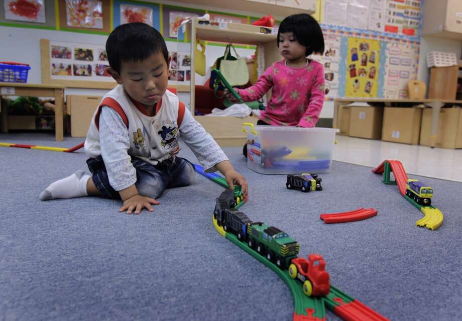 David Zhu and Cathy Zeng play with a train set at Chinatown's Little Sprouts Child Development Center in San Francisco, Calif. on Wednesday, June 12, 2013.