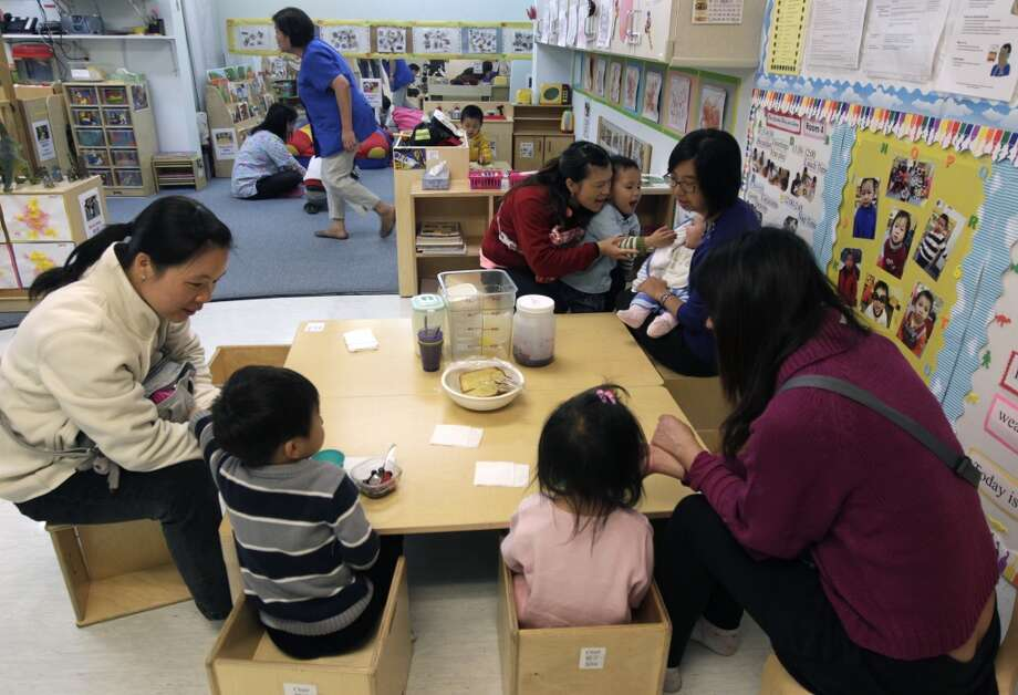 Parents with their children join the preschool's staff at Chinatown's Little Sprouts Child Development Center in San Francisco, Calif. on Wednesday, June 12, 2013.