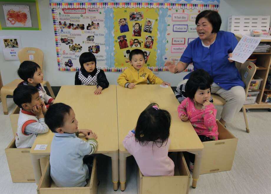 Associate teacher Haisinh Nguyen (right) teaches the alphabet to a group of 3 1/2-year-olds at Chinatown's Little Sprouts Child Development Center in San Francisco, Calif. on Wednesday, June 12, 2013.