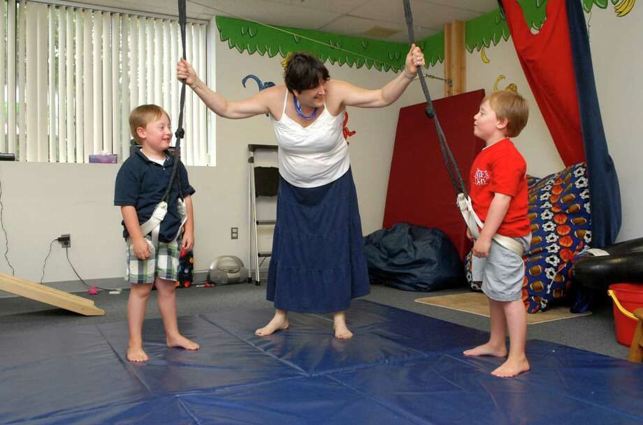 Crae Akerson, owner of Celebrating Children ( Pediatric Occupational Therapy ) in Stamford, Conn., works with twins Jack and Brian Donovan on Monday June 17, 2013. Photo: Dru Nadler / Stamford Advocate Freelance
