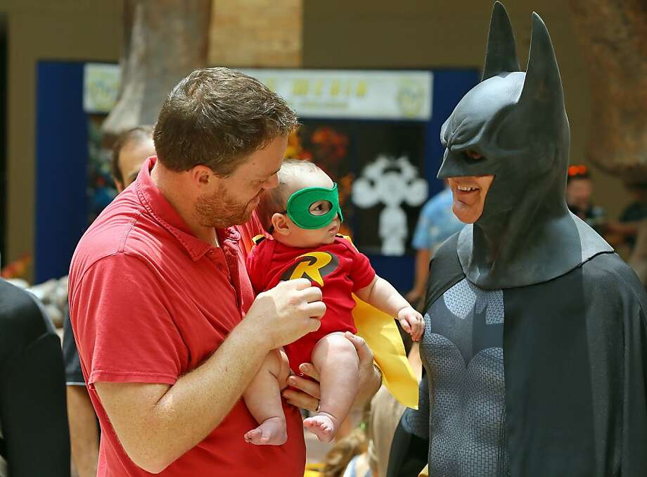 Meet your future guardian: David Carney introduces his 6-month-old son, Jackson, to the Dark Knight during Superhero Day at Fernbank Museum of Natural History in Atlanta. Photo: Curtis Compton, Associated Press
