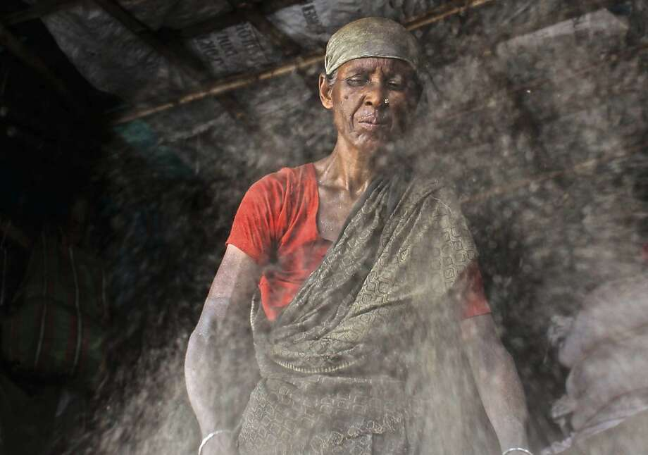 Engulfed in a cloud of dust, a Bangladeshi woman works at a recycling center in Dhaka. Photo: A.M. Ahad, Associated Press