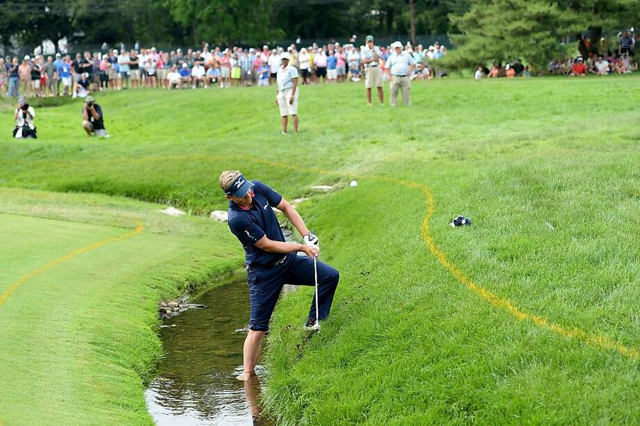 Bogey man:Luke Donald plants a foot in a stream to hit his fourth shot on the fourth hole during his disastrous final round of the U.S. Open at Merion. He had a double bogey and five bogeys on the front nine. Photo: Ross Kinnaird, Getty Images