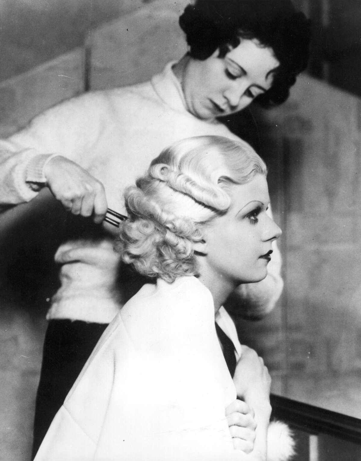 Jean Harlow (1911 - 1937), American film actress, having her famous platinum blonde hair set.