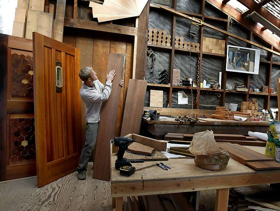 Yorgen Kvinsland checks a redwood plank that he reclaimed from a nearby river, where it lay for decades, for a new door. Photo: Brant Ward, The Chronicle