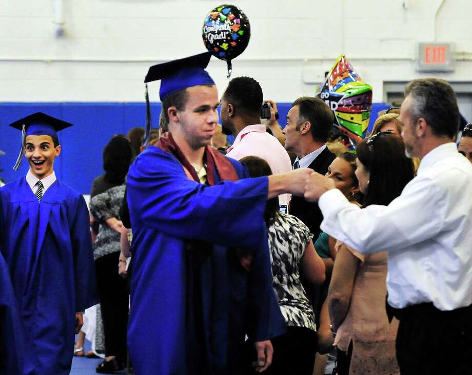 Collin McCarthy fist bumps his teacher, Jim Mills, during the processional as Henry Abbott Technical School holds graduation exercises in the Danbury, Conn, high school Monday, June 17, 2013. Photo: Michael Duffy / The News-Times