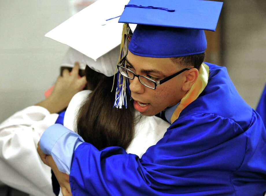 Geordy Hernandez hugs a fellow grad as Henry Abbott Technical School holds graduation exercises in the Danbury, Conn, high school Monday, June 17, 2013. Photo: Michael Duffy / The News-Times