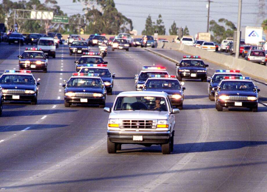 California Highway Patrol officers follow a Ford Bronco driven by Al Cowlings in Los Angeles as O.J. Simpson hides in the rear seat. Simpson's subsequent trial became a national obsession.  Photo: AL SCHABEN, Los Angeles Times