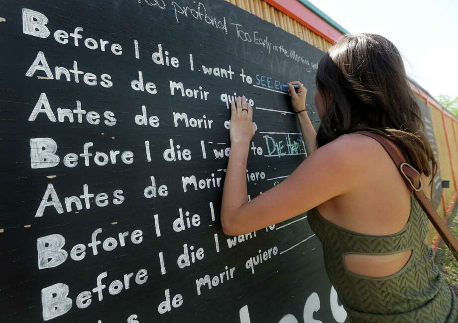 "Leah Malfitano stops to write a note on a public display board called ""Before I die"" on Thursday, June 6, 2013, which was constructed by Lorie Solis after her father was killed as he was riding his bike in Bandera, last year. Photo: San Antonio Express-News / © 2012 San Antonio Express-News"