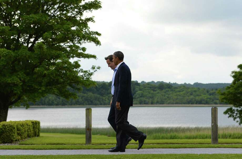 British Prime Minister David Cameron (left) and President Barack Obama walk together Monday  as world leaders arrrive for the G8 Summit in Northern Ireland.  The conflict in Syria was expected to dominate the  summit. Photo: Jewel Samad, Getty Images