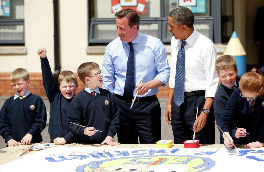 President Barack Obama, center right, and British Prime Minister David Cameron, center left, help students as they work on a school project about the G-8 summit during a visit to the Enniskillen Integrated Primary School in Enniskillen, Northern Ireland, Monday, June 17, 2013. The visit takes place before leaders from the G-8 nations are to gather to discuss the ongoing conflict in Syria, and free-trade issues. (AP Photo/Matt Dunham, Pool) Photo: Matt Dunham, Pool / AP Pool