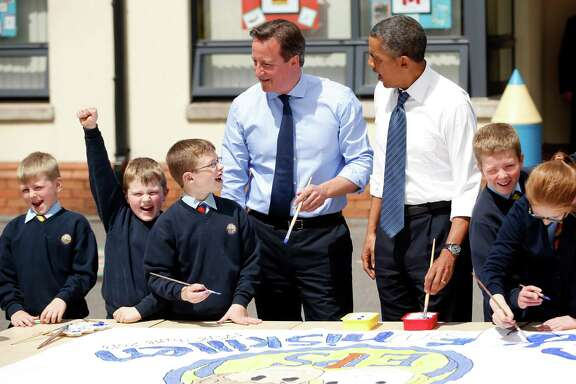 President Barack Obama, center right, and British Prime Minister David Cameron, center left, help students as they work on a school project about the G-8 summit during a visit to the Enniskillen Integrated Primary School in Enniskillen, Northern Ireland, Monday, June 17, 2013. The visit takes place before leaders from the G-8 nations are to gather to discuss the ongoing conflict in Syria, and free-trade issues. (AP Photo/Matt Dunham, Pool)