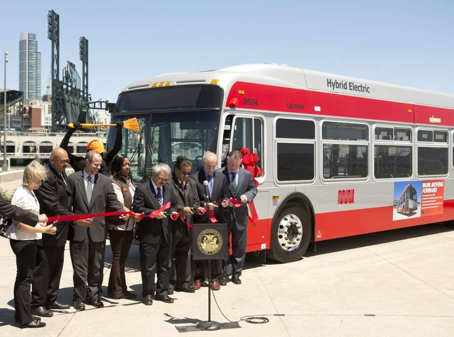 Mayor Ed Lee and other city officials cut a ribbon during a news conference during the launch of Muni's new bio-diesel hybrid buses Monday, June 17, 2013 in San Francisco, Calif.
