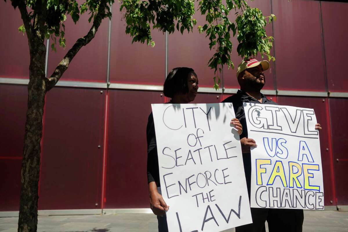 Protestors show off handmade signs during a rally by taxi drivers to demand legal regulation of ridesharing companies Monday, June 17, 2013, at Seattle City Hall in downtown Seattle. The Western Washington Taxicab Operators Association (WWTOA) delivered a petition with more than 500 signatures to the Seattle City Council in an effort to encourage regulation of such companies as Lyft, Sidecar and UBERx.