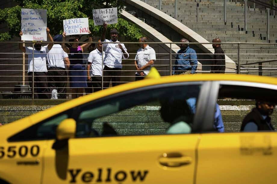 Fronted by a line of honking taxis, taxi drivers and protestors alike picket at a rally in demand of legal regulation for ridesharing companies Monday, June 17, 2013, at Seattle City Hall in downtown Seattle. The Western Washington Taxicab Operators Association (WWTOA) delivered a petition with more than 500 signatures to the Seattle City Council in an effort to encourage regulation of such companies as Lyft, Sidecar and UBERx. Photo: JORDAN STEAD, SEATTLEPI.COM / SEATTLEPI.COM