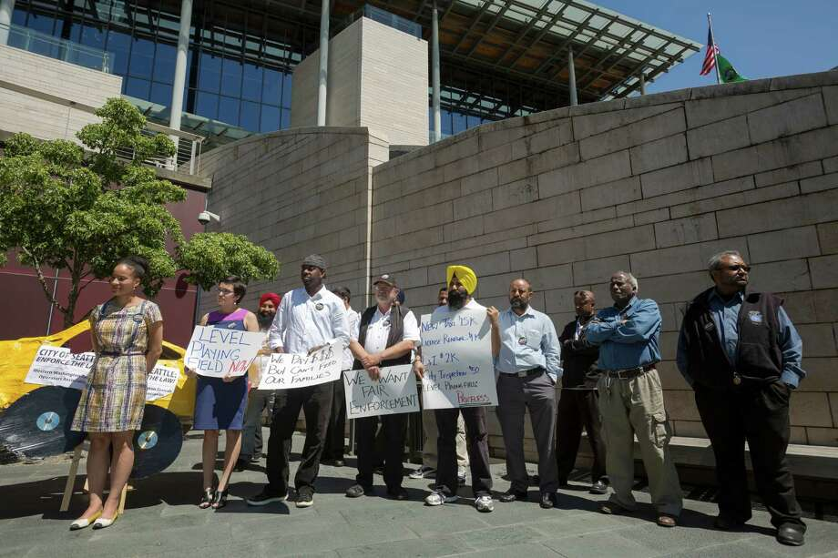 Taxi drivers and protestors speak to media in demand of legal regulation for ridesharing companies during a rally Monday, June 17, 2013, at Seattle City Hall in downtown Seattle. The Western Washington Taxicab Operators Association (WWTOA) delivered a petition with more than 500 signatures to the Seattle City Council in an effort to encourage regulation of such companies as Lyft, Sidecar and UBERx. Photo: JORDAN STEAD, SEATTLEPI.COM / SEATTLEPI.COM