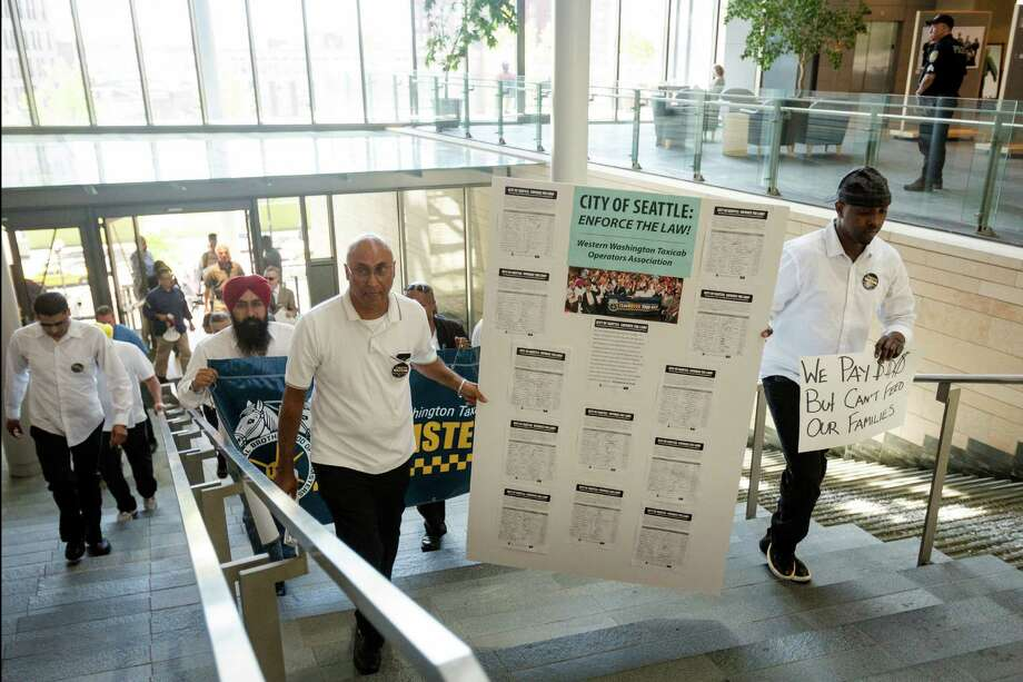 Taxi drivers and protestors march on Seattle City Hall to present a petition with more than 500 signatures to demand legal regulation for ridesharing companies Monday, June 17, 2013, at Seattle City Hall in downtown Seattle. Photo: JORDAN STEAD, SEATTLEPI.COM / SEATTLEPI.COM