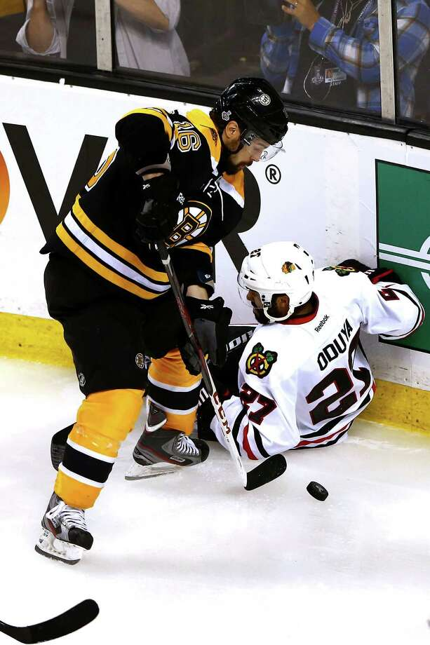 BOSTON, MA - JUNE 17: Kaspars Daugavins #16 of the Boston Bruins handles the puck as Johnny Oduya #27 of the Chicago Blackhawks falls to the ice in Game Three of the 2013 NHL Stanley Cup Final at TD Garden on June 17, 2013 in Boston, Massachusetts. Photo: Elsa, Getty Images / 2013 Getty Images