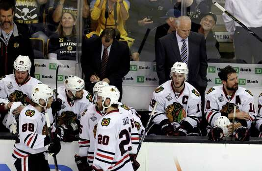 Chicago Blackhawks head coach Joel Quenneville, right, team captain Jonathan Toews (19) and their team pause during a break in pay in the third period in Game 3 of the NHL hockey Stanley Cup Finals against the Boston Bruins in Boston, Monday, June 17, 2013. (AP Photo/Charles Krupa) Photo: Charles Krupa, Associated Press / AP