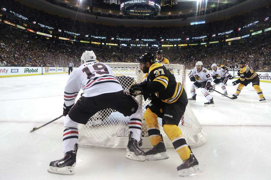 BOSTON, MA - JUNE 17: Jonathan Toews #19 of the Chicago Blackhawks tries a shot on goal against Tuukka Rask #40 and Patrice Bergeron #37 of the Boston Bruins defends in Game Three of the 2013 NHL Stanley Cup Final at TD Garden on June 17, 2013 in Boston, Massachusetts. Photo: Harry How, Getty Images / 2013 Getty Images