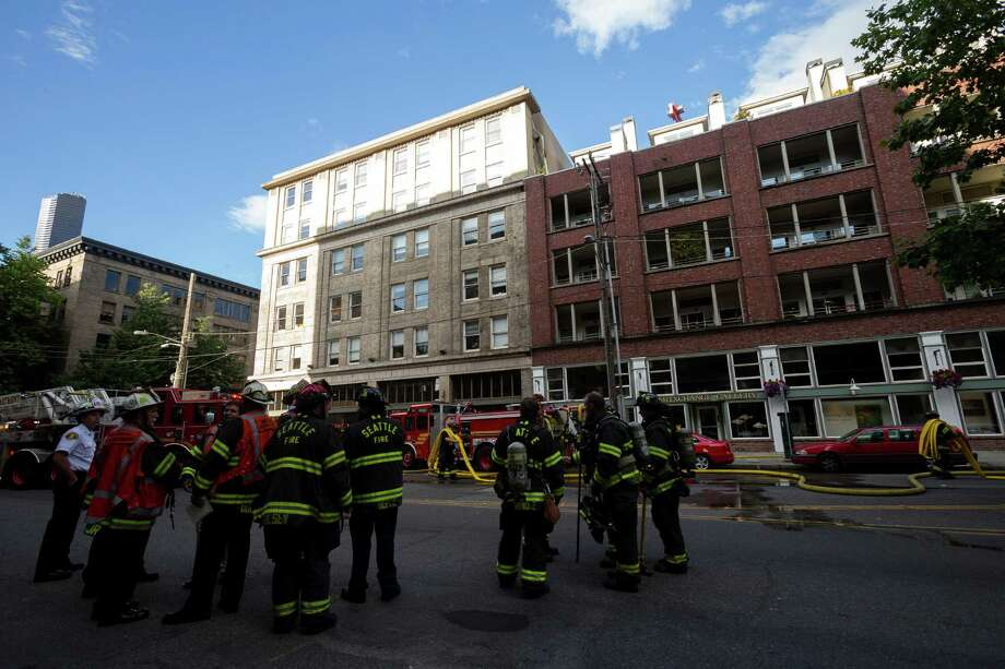 Firefighters work to extinguish a barbecue fire that extended to a deck and injured one patient in her sixties Monday, June 17, 2013, at 526 First Avenue South in Seattle. Firefighters first contained fire to the fifth floor unit of the building and then finished it off. Photo: JORDAN STEAD, SEATTLEPI.COM / SEATTLEPI.COM