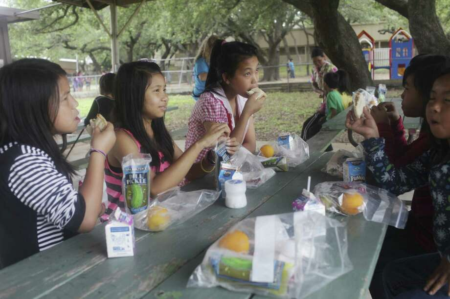 Children of refugee families from Thailand have lunch outside St. Francis Episcopal Church on Friday.  Photo: Abbey Oldham, San Antonio Express-News