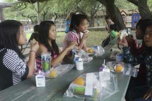 Children of refugee families from Thailand have lunch outside St. Francis Episcopal Church on Friday.