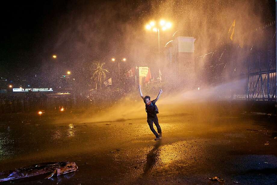 JAKARTA, INDONESIA - JUNE 17:  A protestor runs as police fire a water canon during a demonstration in front of the Indonesian parliament against a proposed rise in fuel prices on June 17, 2013 in Jakarta, Indonesia. Thousands of Indonesians protested around the country against the controversial fuel price hike which is set to be decided by parliament Monday. (Photo by Ed Wray/Getty Images) *** BESTPIX *** Photo: Ed Wray, Getty Images