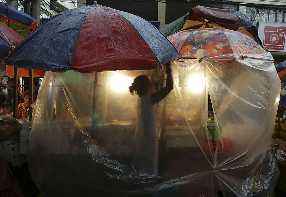 A Filipino woman vendor fixes a plastic sheet to protect fruits that she sells during rain in downtown Manila, Philippines on Monday June 17, 2013. (AP Photo/Aaron Favila) Photo: Aaron Favila, Associated Press