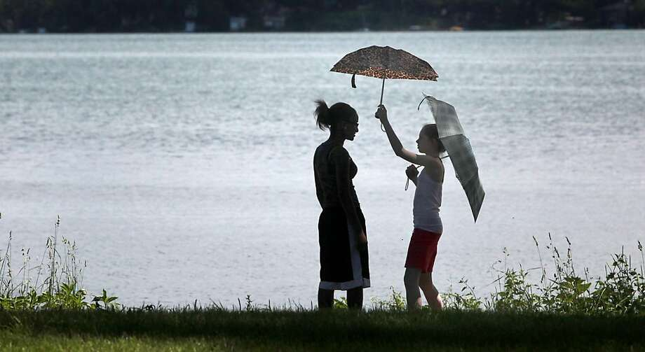 Donette Johnson, left, and Cheri Grant stand in the shade umbrellas during a fishing outing along the shores of Lake Monona at Yahara Place Park in Madison, Wis. Monday, June 17, 2013. (AP Photo/Wisconsin State Journal, John Hart) Photo: John Hart, Associated Press