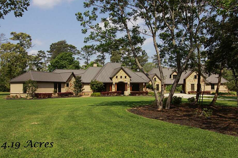 This sprawling 1.5-story home is located on more than four picturesque acres in a private gated neighborhood.