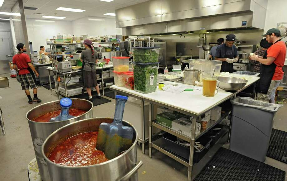 Workers are busy making recipes in the kitchen at the new Honest Weight Food Co-op at 100 Watervliet Ave. on Monday, June 17, 2013 in Albany, N.Y. The soft opening is Wednesday. (Lori Van Buren / Times Union) Photo: Lori Van Buren / 10022837A