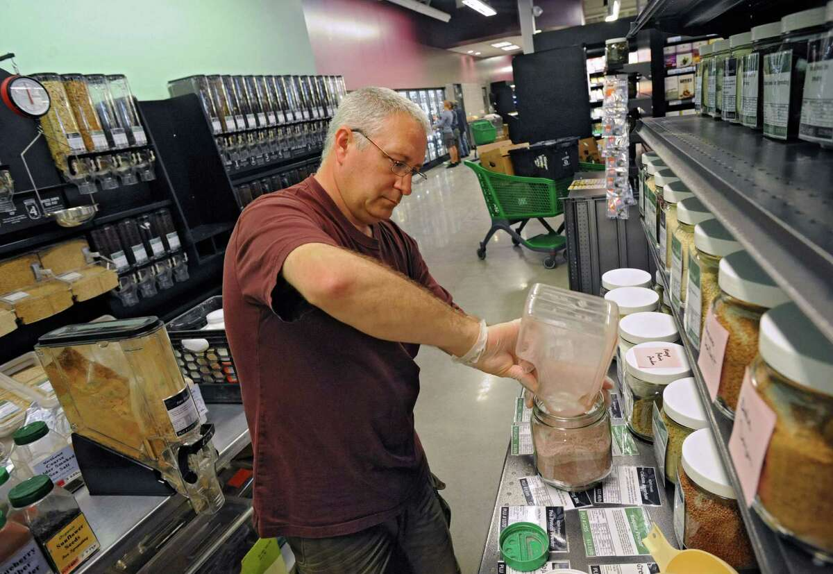 Member worker Randall Collura of Delmar is busy setting up the bulk area at the new Honest Weight Food Co-op at 100 Watervliet Ave. on Monday, June 17, 2013 in Albany, N.Y. The soft opening is Wednesday. (Lori Van Buren / Times Union)