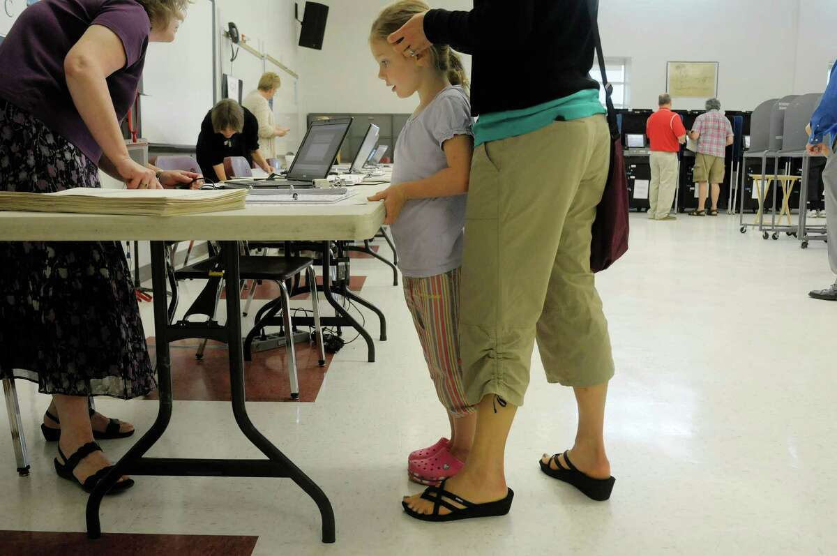 Eve Bratten, 5, waits with her mom, Sally Bratten, who signs in before voting on the school budget at Niskayuna High School on Tuesday morning, June 18, 2013 in Niskayuna, NY. The school district's first budget was defeated. (Paul Buckowski / Times Union)