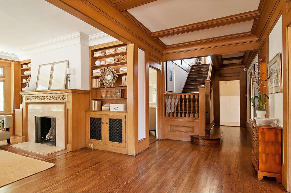 The foyer features a beamed ceiling and leads to a hardwood staircase.