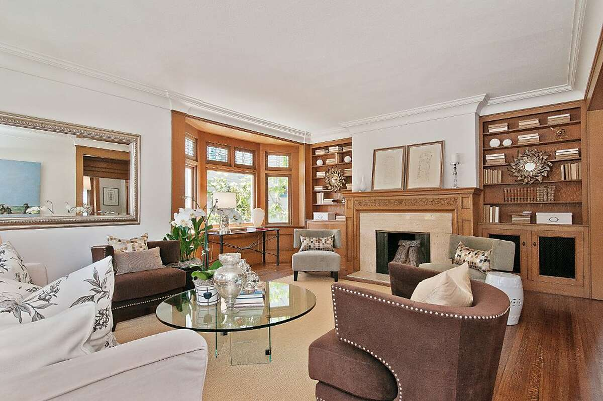 The hardwood fireplace surround has decorative engravings and is surrounded by built-in bookshelves.