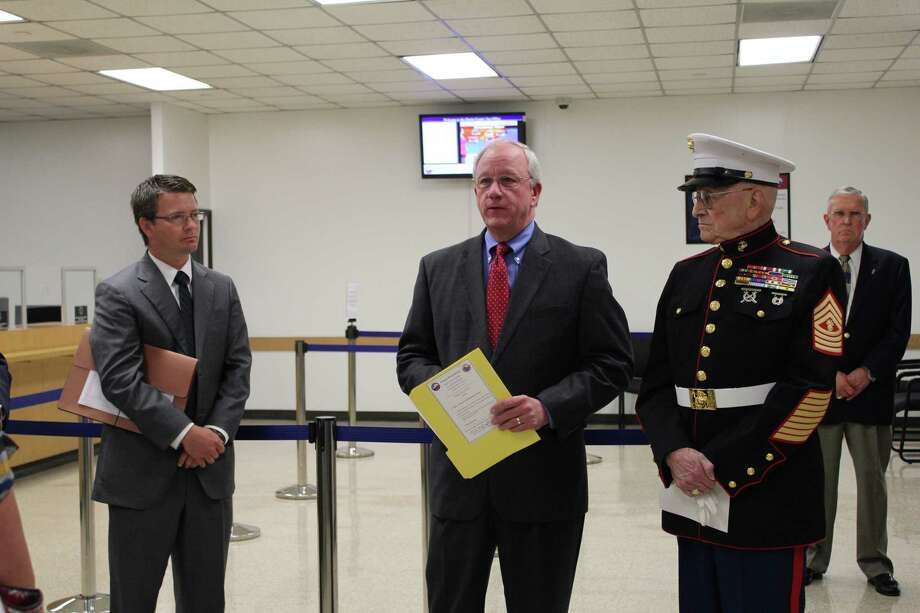 Retired U.S. Marine Corps Master Gunnery Sgt. Harold Tetrick, right, received the first license plate issued at the reopened Kyle Chapman Branch of the Harris County Tax Office June 10. From left are Precinct 2 Commissioner Jack Morman and Harris County Tax Assessor-Collector Mike Sullivan. Photo: Courtesy Of Harris County Tax Of
