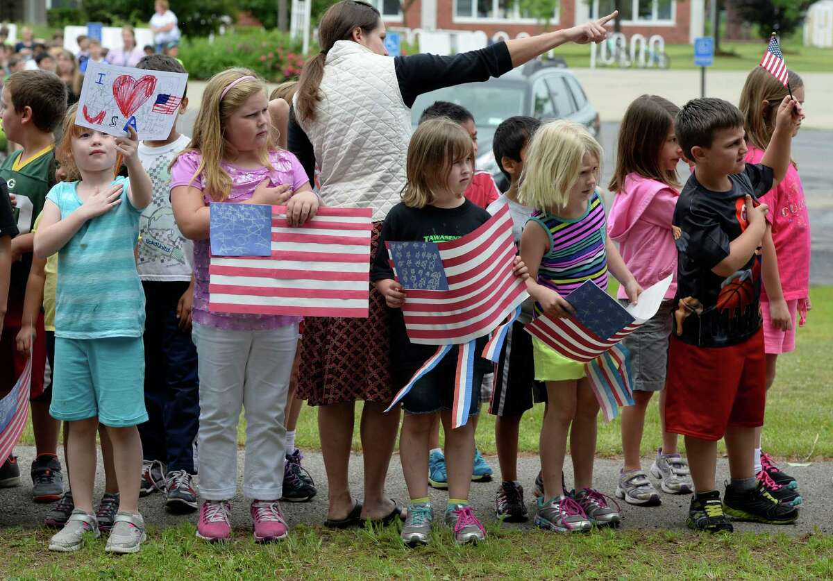 Students from the Pine Bush Elementary School line up outside their school June 18, 2013, to show their respect for Lt. Col. Todd Clark as his funeral procession passes the school in Guilderland, N.Y. (Skip Dickstein/Times Union)