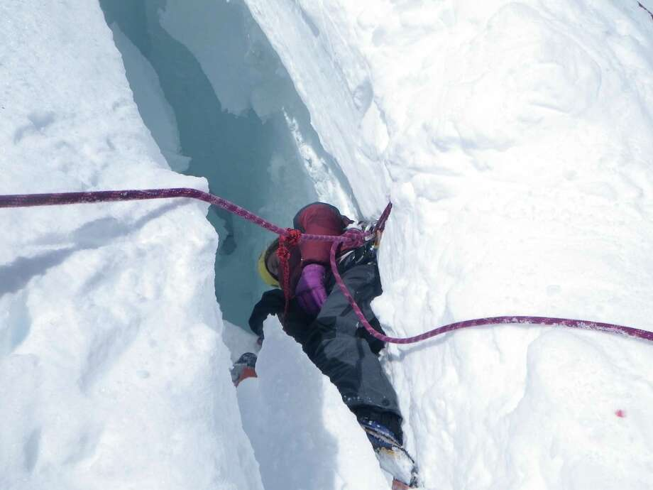 June 21, 2012 By Stacy Wren Noelle Smith, as she dangles in a crevasse on the face of Mount Rainier in the wake of an accident involving four Texas climbers on June 21, 2012. Smith, who was then 18 and fresh out of high school in Dallas, plunged into the seemingly bottomless hole in the ice. If she had not fallen into the hole, and ended up acting as an anchor for the others, all would have most certainly died by plunging further down the ice, authorizes have said.  Smith recalls that she could not see the bottom of the crevasse. Not long after the photo was taken, Smith was pulled to safety with the help of Peter Ramos, a Montana mountain-climbing guide who was the first rescuer to reach them. Photo: Stacy Wren / handout